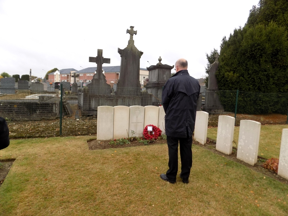 LBSG archaeologist, Brian Powell, having laid a rose at the collective grave