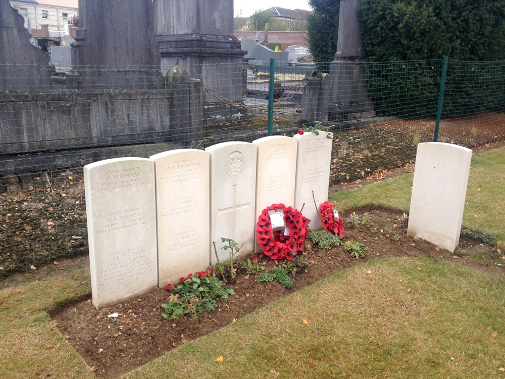 The new collective grave with roses and wreaths laid in tribute